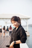 Svart skjorta för asiatiska kvinnor som står träterrassen Royaltyfri Foto