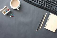 Svart skrivbord med kaffekoppen, tangentbordet, anteckningsboken och pennan som in förläggas royaltyfri fotografi
