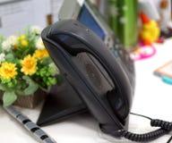 Svart skrivbords- telefon i kontoret arkivfoto