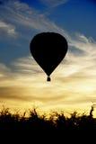 Svart skugga av en ballong för varm luft på solnedgången Arkivfoto