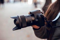 Svart SLR kamera i händerna av en flicka arkivfoton