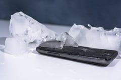 Svart smartphone som frysas i is Foto för abstrakt objekt royaltyfri bild