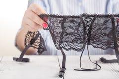 Svart snör åt bältet för strumpor i kvinnlig hand trendigt begrepp arkivfoto