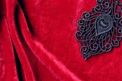 Svart snör åt på röd sammet royaltyfri fotografi