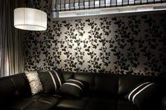 Svart soffa med en lampskärm bredvid den av hängande lampor Royaltyfri Fotografi