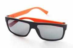 Svart solglasögon och orange isolat arkivfoto