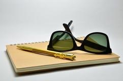 Svart solglasögon på den bruna anteckningsboken och penna Arkivbild