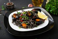 svart spagetti Svart havs- pasta med musslor över svart bakgrund Arkivfoton