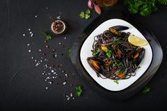 svart spagetti Svart havs- pasta med musslor över svart bakgrund Arkivbilder