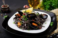 svart spagetti Svart havs- pasta med musslor över svart bakgrund Royaltyfria Bilder