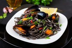 svart spagetti Svart havs- pasta med musslor över svart bakgrund Arkivfoto