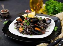 svart spagetti Svart havs- pasta med musslor över svart bakgrund Arkivbild