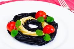 Svart spagetti med den bläckfiskfärgpulver, tomaten och basilika Mediterra arkivfoto
