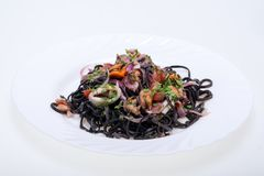Svart spagetti med skaldjur och grönsaker Arkivbild