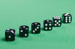 Svart spela tärning för kasino på en grön bakgrund royaltyfri bild