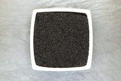 Svart spiskummin Sativa Nigella eller Kalonji frö i den vita plattan på vit stenbakgrundsyttersida med fritt utrymme Royaltyfri Foto