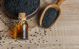 Svart spiskumminfrö och nödvändig olja med bunken och träskyffel eller sked royaltyfria bilder