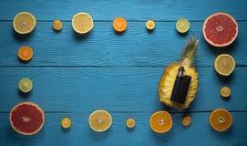 Svart sprejflaska som omges av citruns Royaltyfri Bild