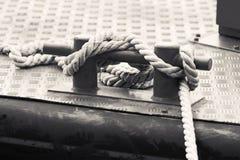 Svart stålpollare med rep som monteras på ett skeppdäck Arkivfoto
