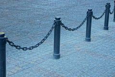 Svart staket med järnkedjor och pelare på trottoaren på stadsgatan royaltyfria bilder