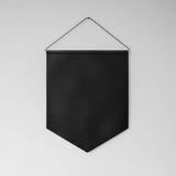 Svart standert som hänger på vägggrå färgbakgrunden Arkivfoto