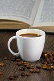 Svart starkt kaffe på tabellen och läseboken Arkivfoton