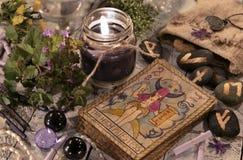 Svart stearinljus med de tarokkorten och runorna Royaltyfria Bilder