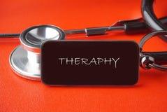 Svart stetoskop på röd bakgrund Royaltyfria Foton