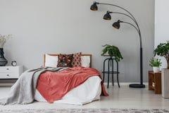 Svart stilfull lampa i det eleganta sovrummet som är inre med den bekväma dubbelsäng, växter och nattduksbordet arkivbild