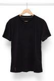 Svart T-tröja som isoleras med hängaren Fotografering för Bildbyråer