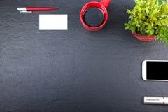 Svart tabell för kontorsskrivbord med datoren, penna och en kopp kaffe, lott av saker Bästa sikt med kopieringsutrymme Arkivfoton
