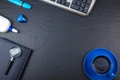 Svart tabell för kontorsskrivbord med datoren, penna och en kopp kaffe, lott av saker Bästa sikt med kopieringsutrymme Arkivfoto