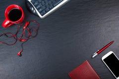 Svart tabell för kontorsskrivbord med datoren, penna och en kopp kaffe, lott av saker Bästa sikt med kopieringsutrymme Royaltyfri Foto