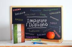Svart tavla i ett italienskt språkklassrum med meddelandet LÄR ITALIENARE Arkivbilder