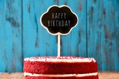 Svart tavla med den lyckliga födelsedagen för text i en kaka, med ett retro Arkivbild