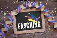 Svart tavla med det tyska ordet för karnevalet - Karneval på träbakgrund arkivfoton