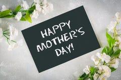 Svart tavla med ett tomt fält som omges av vita blommor på en grå bakgrund lycklig moder s för dag royaltyfria bilder
