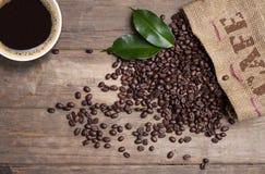 Svart tavla med kaffebönor och en kopp kaffe på naturligt brunt trä royaltyfria bilder