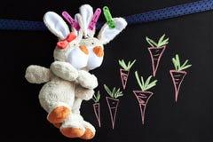 Svart tavla med morötter och leksakkaniner Royaltyfria Bilder