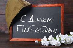 Svart tavla med rysk text: Lyckliga Victory Day Rysk ferie på Maj, 9th Royaltyfria Bilder