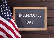 Svart tavla med SJÄLVSTÄNDIGHETSDAGENtext bredvid amerikanska flaggan Fotografering för Bildbyråer