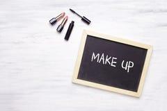 Svart tavla med sminket som är skriftligt på det och kosmetiska produkter på Royaltyfri Foto