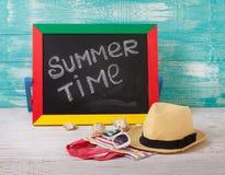 Svart tavla med text är det sommartid, tillbehörsolglasögon, hatten, handduk på trädäck Royaltyfria Foton