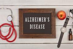 svart tavla med text & x22; Alzheimer& x27; s-disease& x22; , klocka och stetoskop Royaltyfri Fotografi