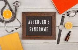svart tavla med text & x22; Asperger& x27; s-syndrome& x22; , böcker, stetoskop, glasögon och klocka royaltyfria bilder