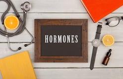 svart tavla med text & x22; Hormones& x22; , böcker, stetoskop och klocka Arkivfoton