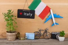 svart tavla med text & x22; Italy& x22; , flagga av Italien, flygplanmodell, liten cykel och resväska, kamera, kompass Royaltyfri Foto