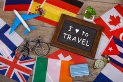 svart tavla med text & x22; Jag älskar till Travel& x22; , flaggor av olika länder, flygplanmodell, liten cykel och resväska royaltyfria foton