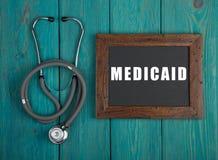 Svart tavla med text & x22; Medicaid& x22; och stetoskop royaltyfri foto