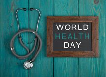 Svart tavla med text & x22; Värld vård- Day& x22; och stetoskop arkivbild